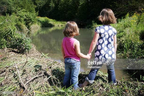Cute Sisters Holding Hands, Playing and Looking at River