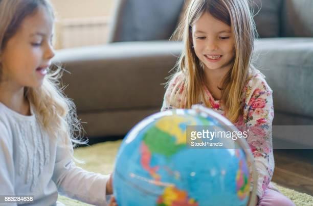 Cute sisters looking at globe
