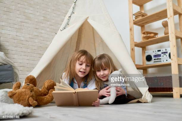 cute sisters reading fairy tale in teepee - teepee stock pictures, royalty-free photos & images