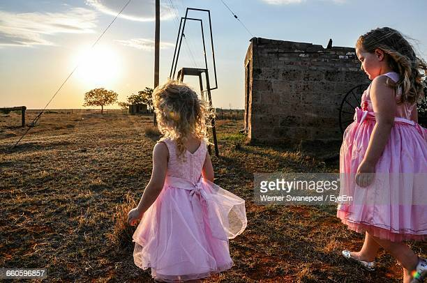 Cute Sisters Walking On Field Against Sky During Sunset