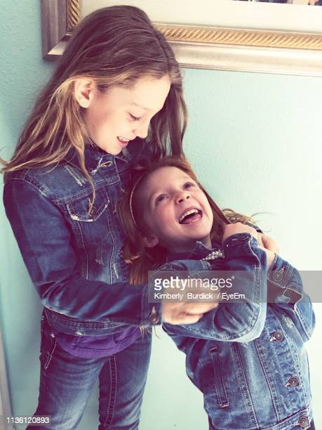cute sisters wearing denim jackets while standing at home - 6 7 anni foto e immagini stock