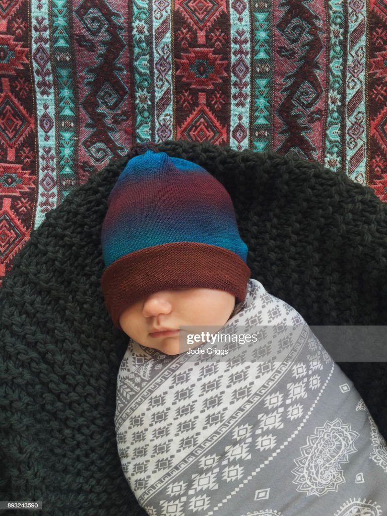 599da5c76 Cute Sleeping Baby Swaddled In A Blanket With Hat Covering Eyes ...