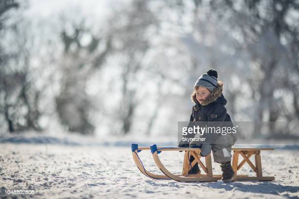 Cute small boy sledging on the snow in nature.
