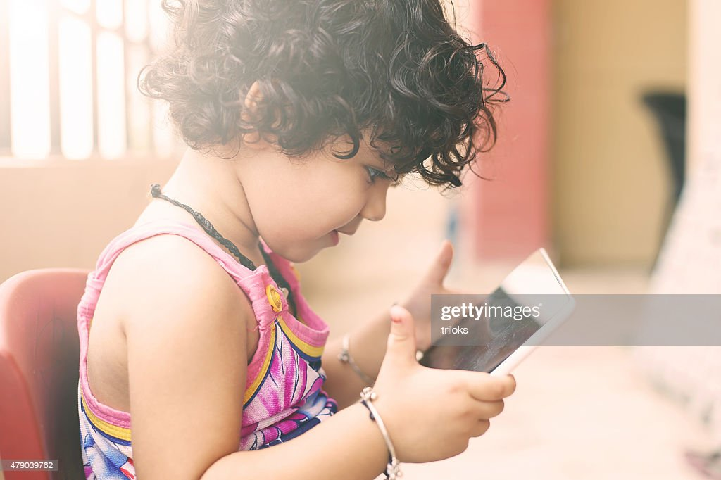 Cute small girl using a digital tablet in balcony : Stock Photo