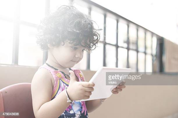 Cute small girl using a digital tablet in balcony