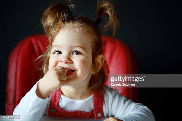Cute smiling baby girl sitting on chair, hand in mouth