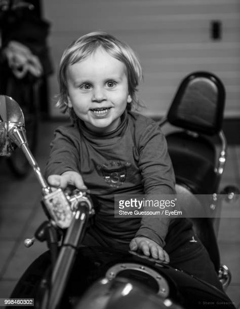 Cute Smiling Boy Sitting On Motorcycle