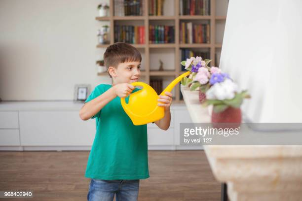 Cute smiling boy watering blooming house plants with watering can