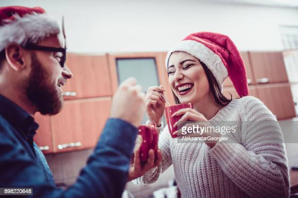 cute smiling couple drinking hot drink at christmas party - eggnog stock photos and pictures