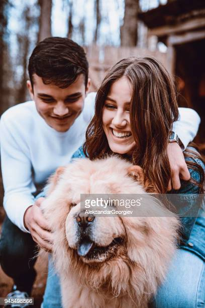 cute smiling couple playing with chow chow dog outdoors - chow dog stock pictures, royalty-free photos & images