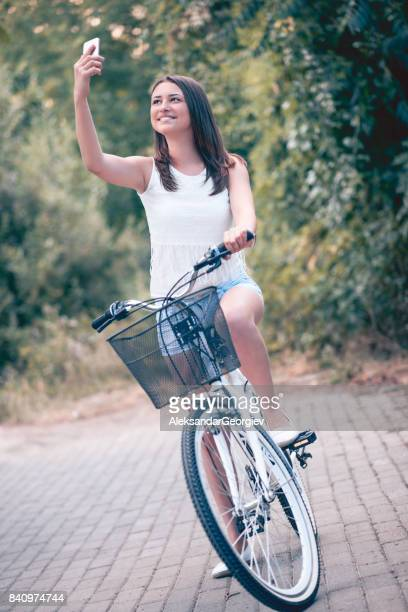 cute smiling female taking selfie during bike ride in city park - macedonia country stock pictures, royalty-free photos & images