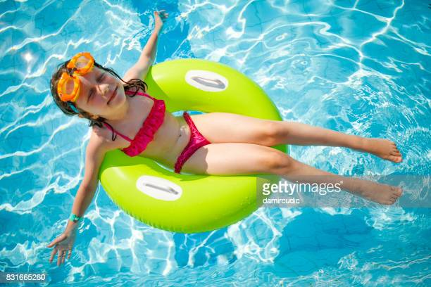 Cute smiling girl floating on a green inflatable ring in swimming pool