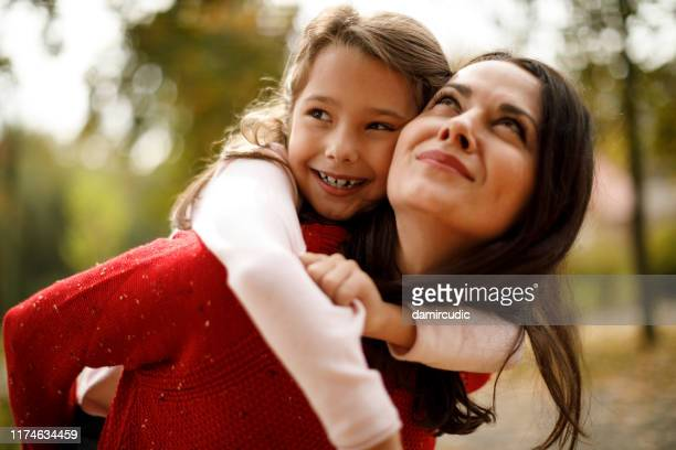 cute smiling girl on a piggy back ride with her mother - damircudic stock photos and pictures