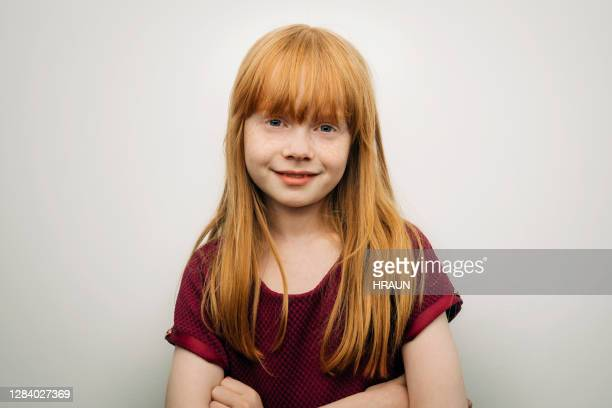 cute smiling girl standing with arms crossed - human age stock pictures, royalty-free photos & images