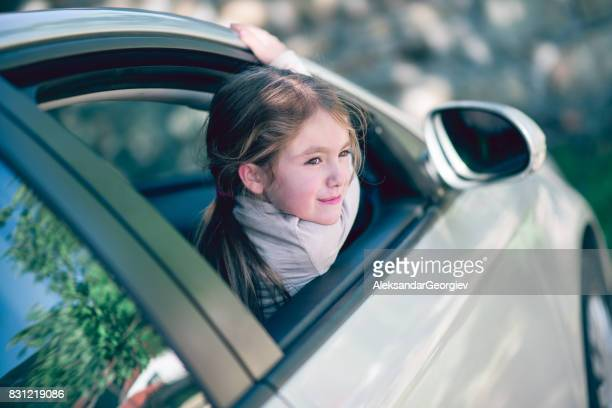 Cute Smiling Little Girl Posing Out of Car Window