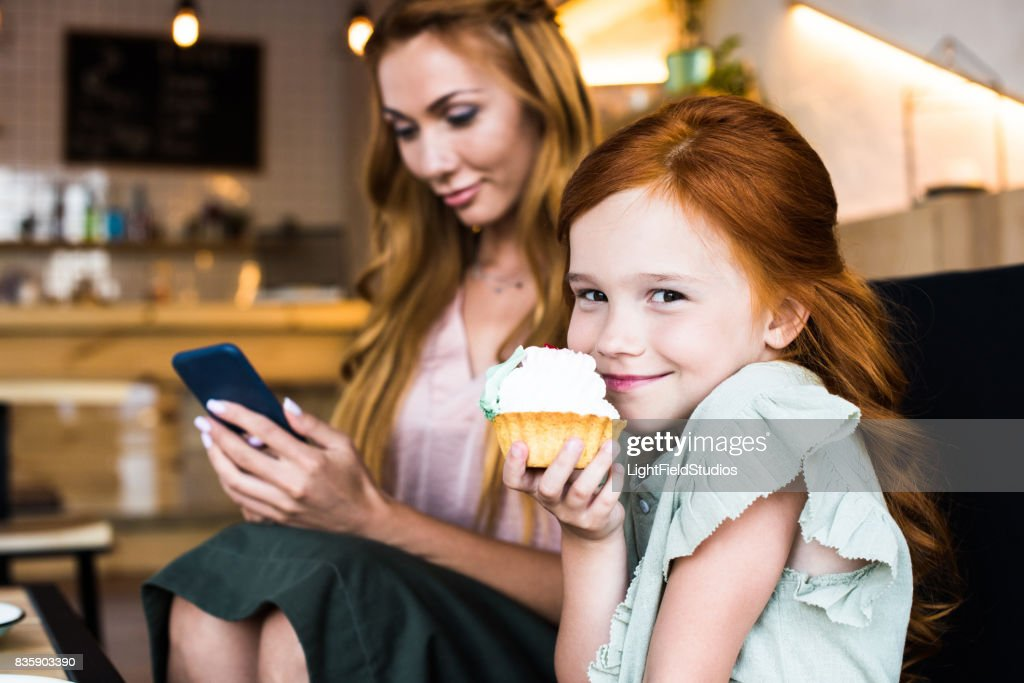 cute smiling redhead girl eating cupcake while mother using smartphone behind : Stock Photo
