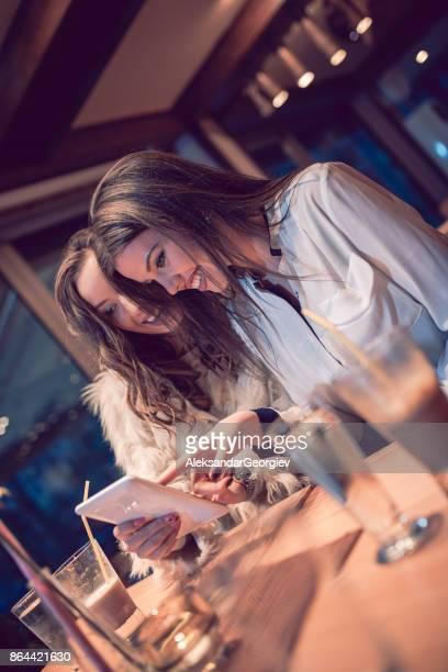 Schattige lachende goed gekleed vrouwtjes surfen het net in Bar