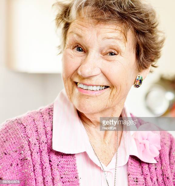 Cute, smiling woman in her 80s is happily surprised