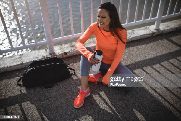cute smiling woman with water bottle relaxing on the bridge - vestito arancione foto e immagini stock