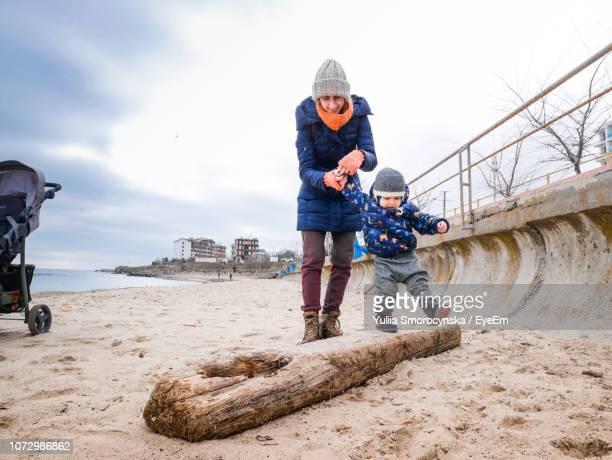 cute son and mother playing on driftwood at beach - odessa ukraine stock pictures, royalty-free photos & images