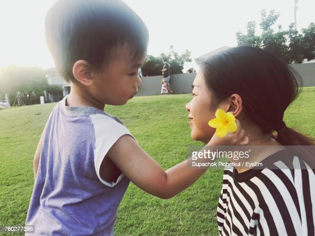 Cute Son Putting Flower In Mother Hair At Park