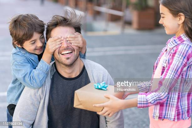 cute soon covering his father's eyes while daughter holds a present for father's day - dia dos pais imagens e fotografias de stock
