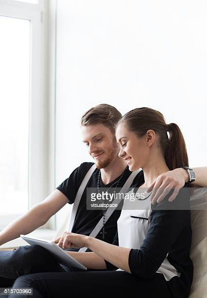 Cute Student Couple Studying Together Using Digital Tablet