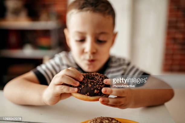 cute sweet blonde child, playing and eating donuts - obsolete stock pictures, royalty-free photos & images