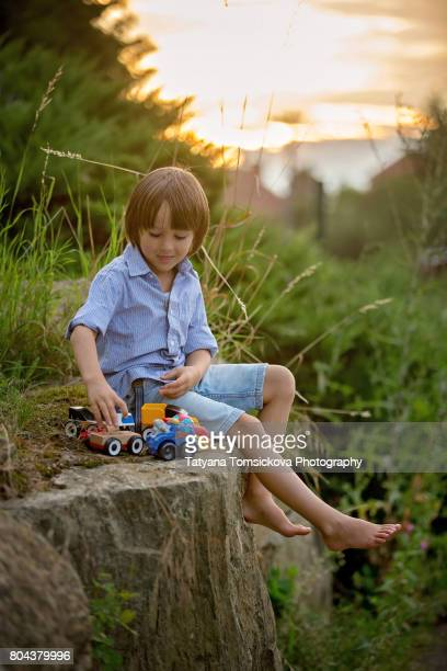 Cute sweet child, boy, playing with car toys on the street in village on sunset, summertime