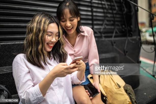 cute taiwanese university students using social media and laughing in front of garage doors - industrial door stock pictures, royalty-free photos & images