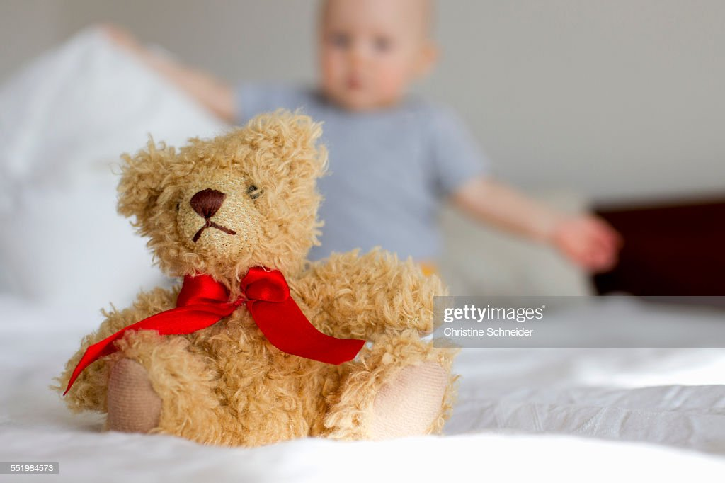cute teddy bear sitting up in bed in front of baby girl stock photo