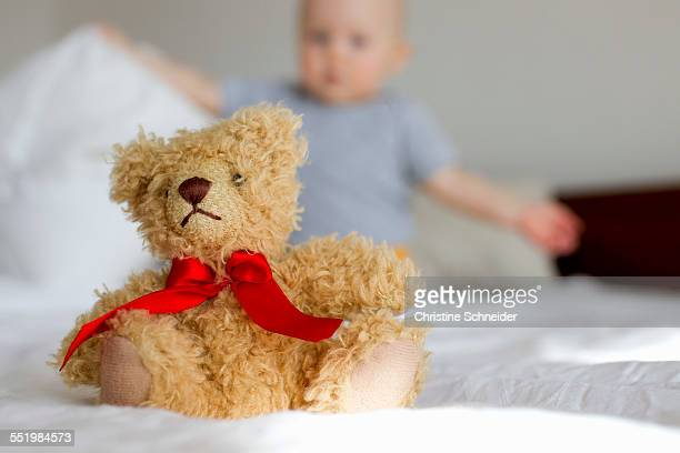 Cute teddy bear sitting up in bed in front of baby girl