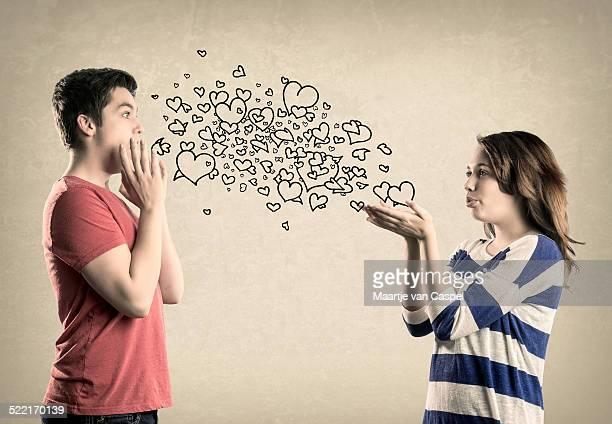 Mignon jeune couple baisers de coeurs de soufflage /