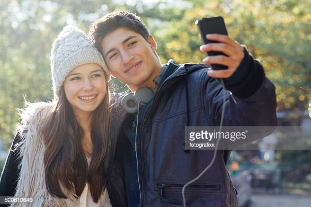 cute teenage couple takes a selfie on nature background