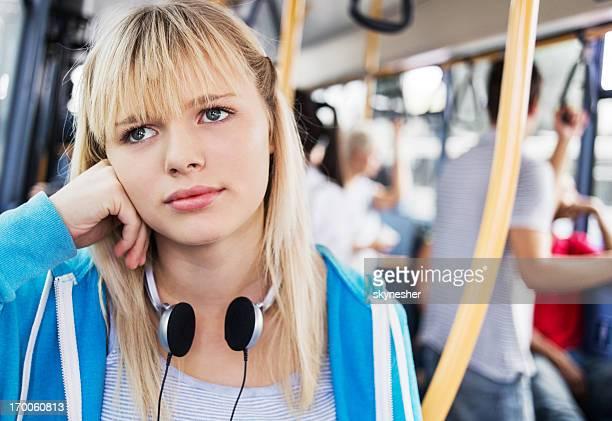 Cute teenage girl commuting by bus.