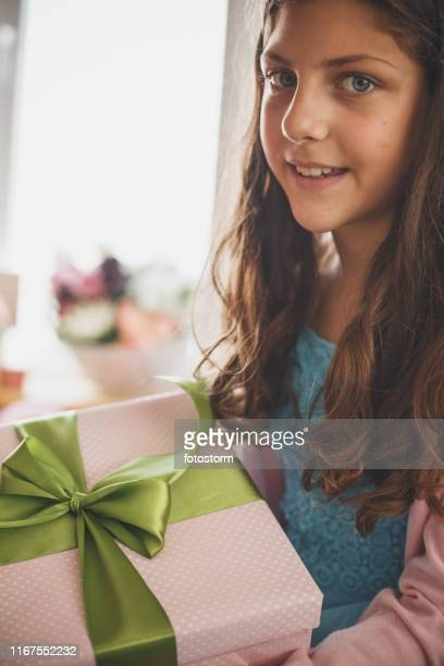 Cute teenage girl holding a gift box and smiling