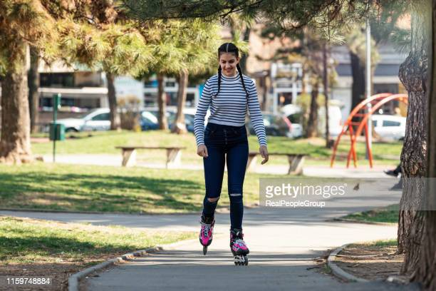 cute teenage girl on the rolling skates in public park - inline skating stock pictures, royalty-free photos & images