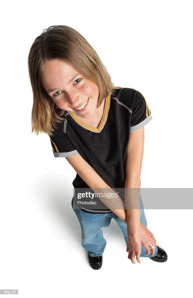 cute teenage girl with shorter straight dark blonde hair wearing a black short sleeved shirt blue jeans and black shoes smiles happily up at the camera and holds her arms and hands outstretched in front of her : Foto de stock