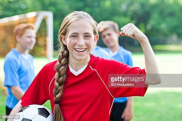 Cute teenage soccer player flexes her muscles during practice