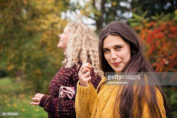 Cute teenager caught eating an apple in orchard.