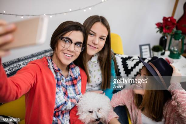 Cute teenagers and a dog taking selife.