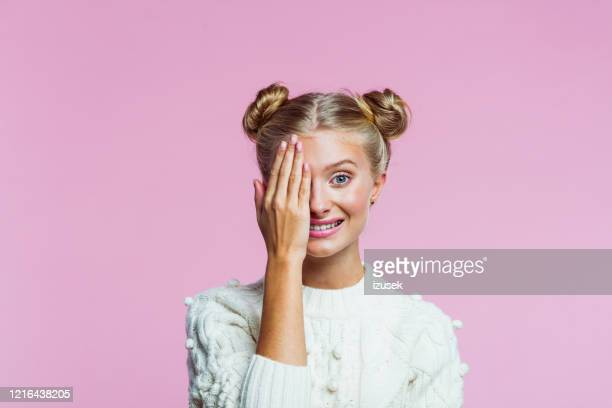 cute teenege girl covering her eye with hand - up do stock pictures, royalty-free photos & images