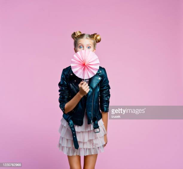 cute teenege girl covering her mouth with origami fans wheel - up do stock pictures, royalty-free photos & images