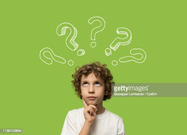 cute thoughtful boy looking up with question marks against green background - 疑問 ストックフォトと画像