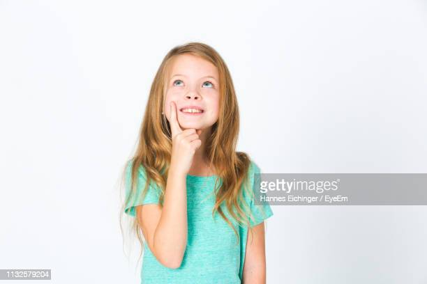 cute thoughtful girl with long hair standing against white background - alleen één meisje stockfoto's en -beelden