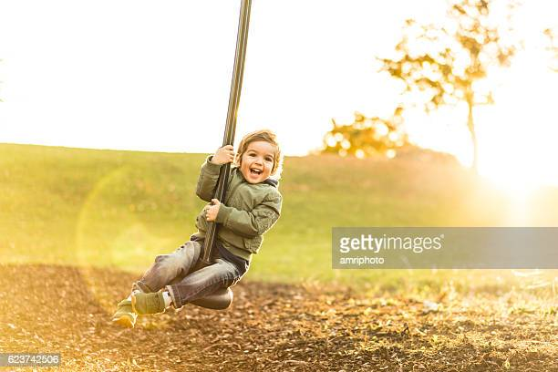 cute three year old boy on a zipline in backlight