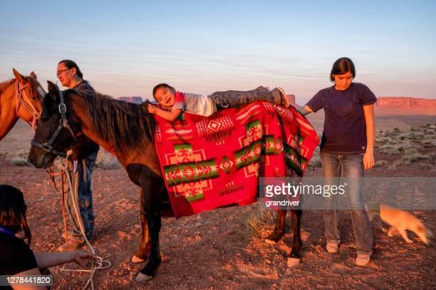 mignon trois ans amérindien navajo garçon navajo couché sur le dos d'un cheval que sa famille se prépare à monter dans le nord de l'arizona au monument valley tribal park sur la réserve navajo au crépuscule - apache photos et images de collection