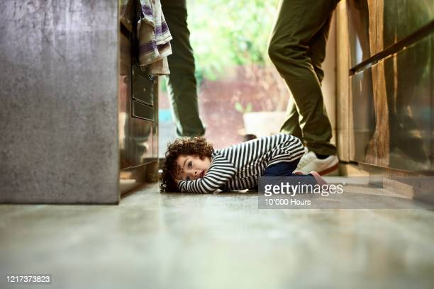 cute toddler boy with curly hair lying on kitchen floor - one baby boy only stock pictures, royalty-free photos & images