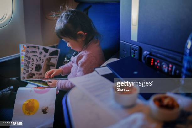 cute toddler boy with headphone in business class on plane. - toddler at airport stock pictures, royalty-free photos & images