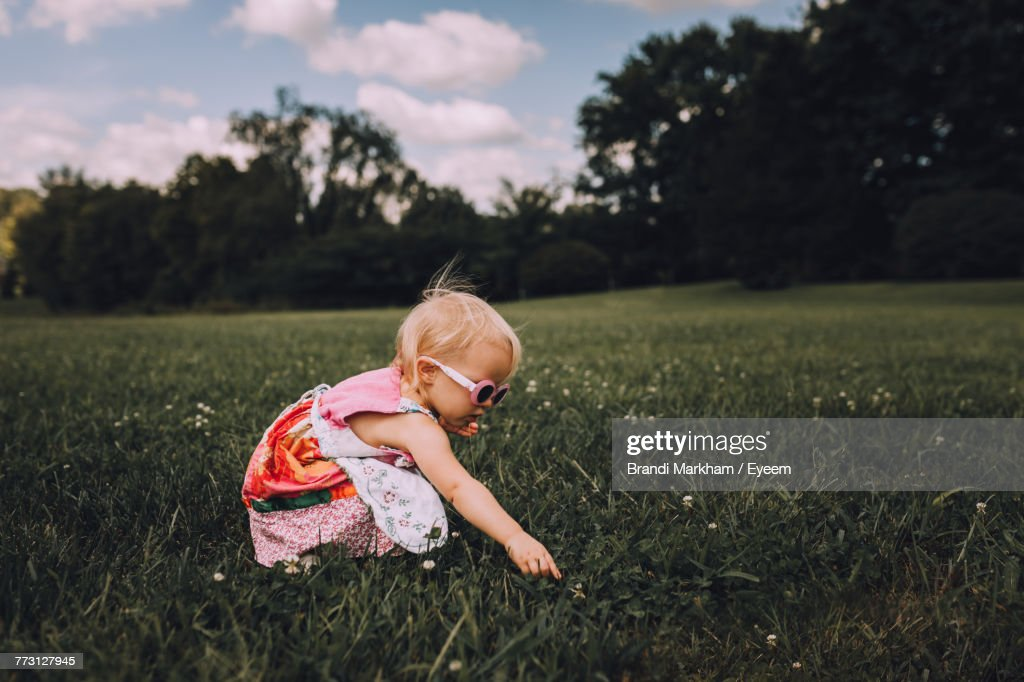 Cute Toddler Girl Crouching On Grassy Field : Stockfoto